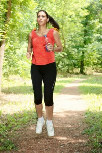 Fitness girl jogging through the woods in summer.